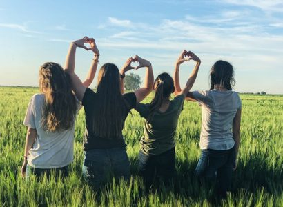 Four women in a field making heart hands