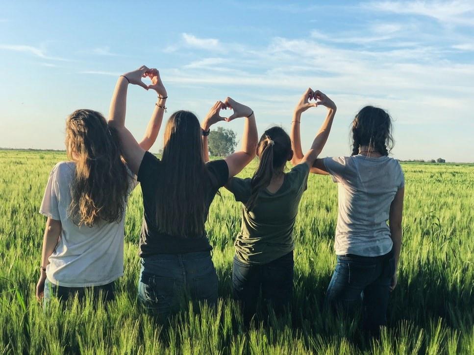 Four women in a field making heart hands
