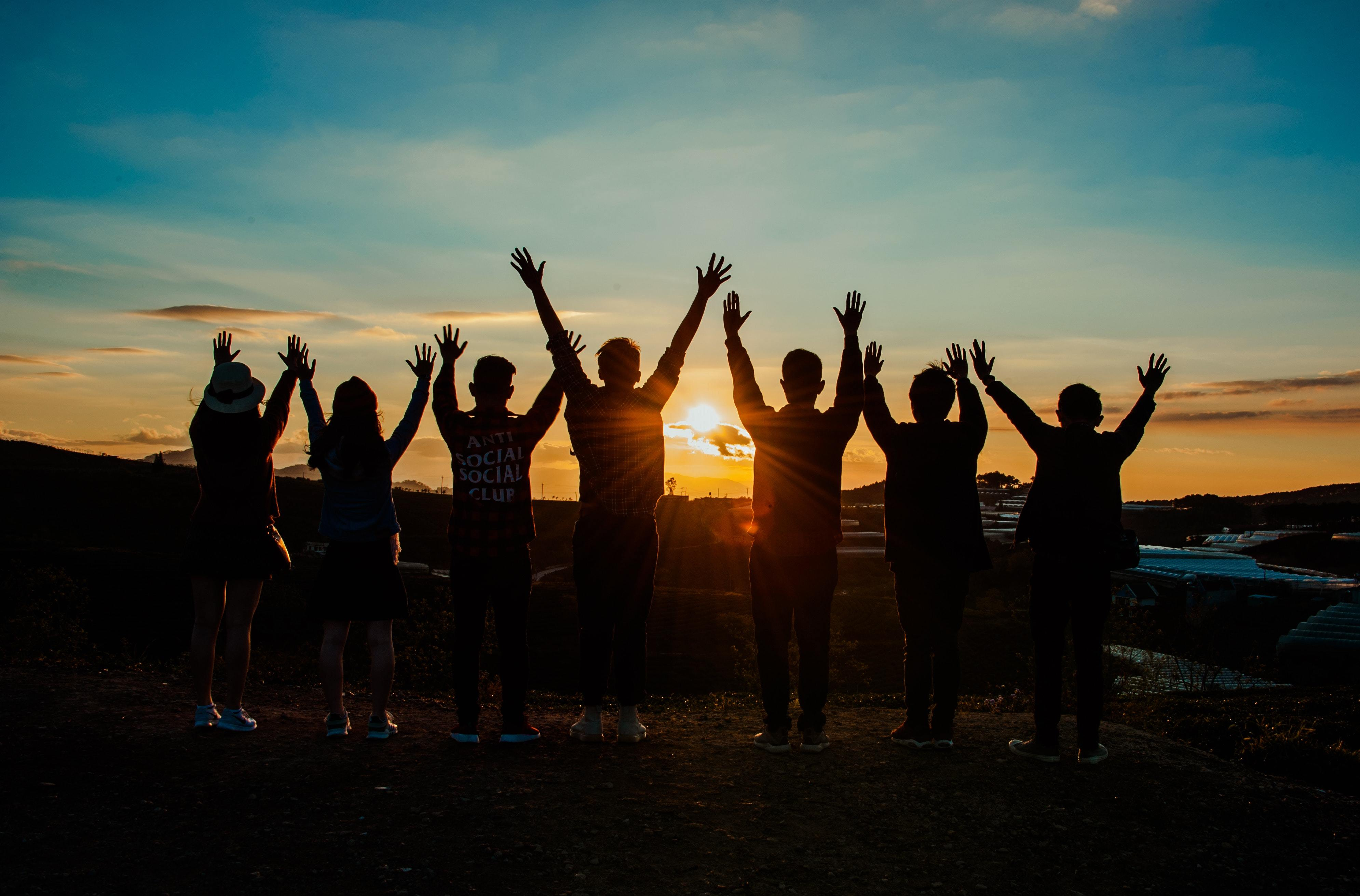Group Of People With Arms Raised Facing Horizon