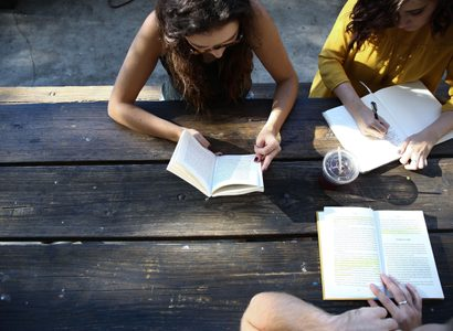 People reading at wooden bench