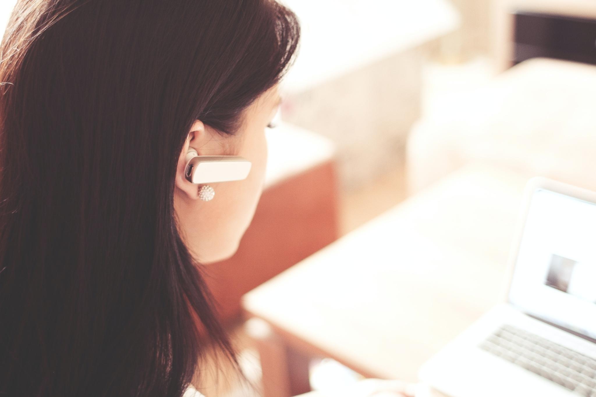 Woman wearing earpiece using laptop