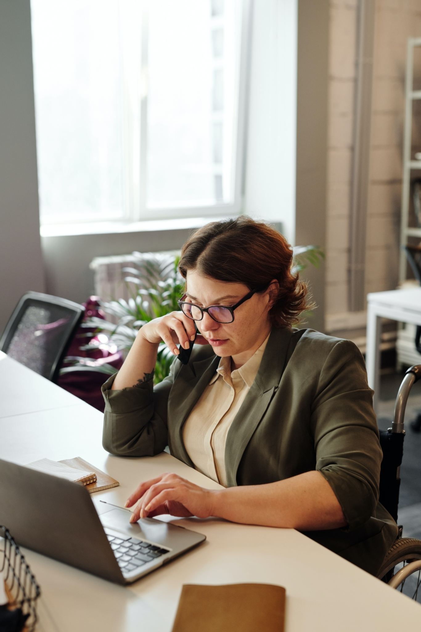 Woman at desk with laptop and mobile